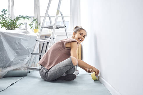 Smiling woman applying adhesive tape on wall while sitting at home - BSZF01721
