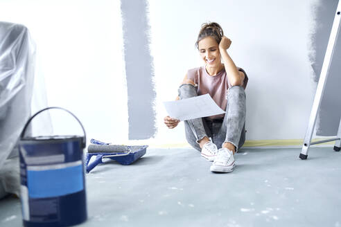 Smiling woman with head in hands holding paper while sitting on floor at home - BSZF01730