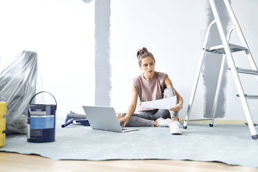 Young woman holding paper while working on laptop at home - BSZF01733
