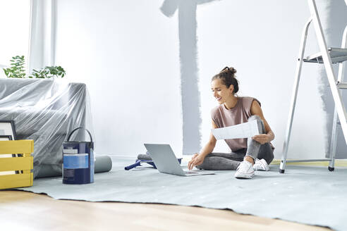 Smiling woman sitting on floor while working on laptop at home - BSZF01736