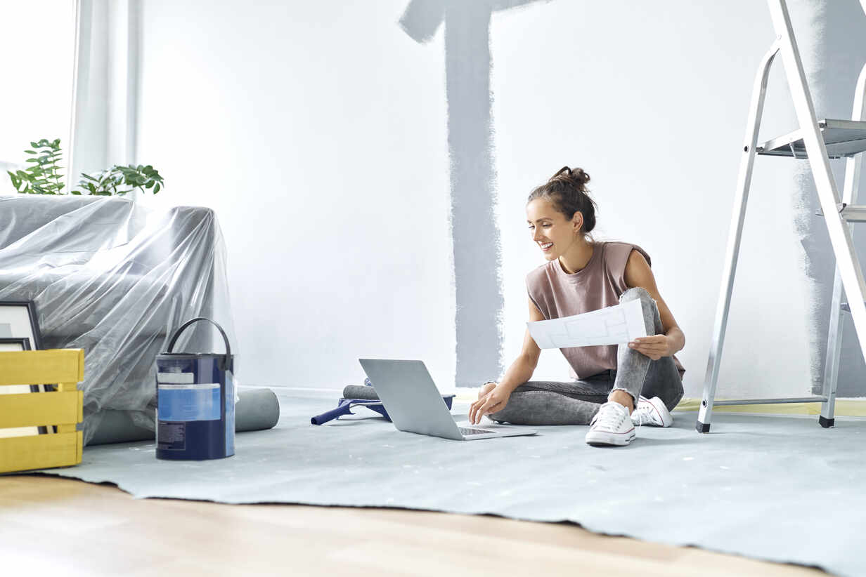 Smiling woman sitting on floor while working on laptop at home - BSZF01736 - Bartek Szewczyk/Westend61