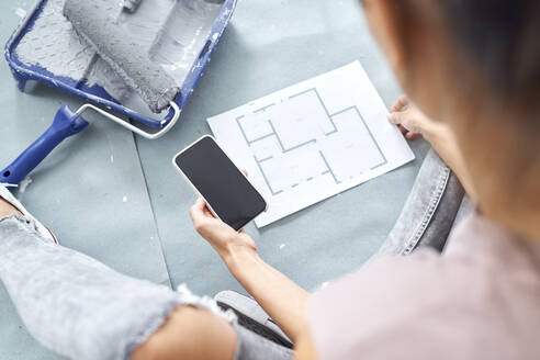Young woman working on design while using mobile phone at home - BSZF01739