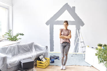 Young woman with arms crossed standing against house painted on wall at home - BSZF01742