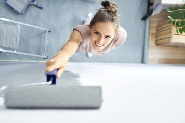 Smiling young woman painting wall with paint roller while standing at home - BSZF01745
