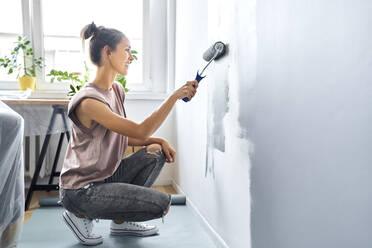 Woman smiling while painting wall at home - BSZF01748