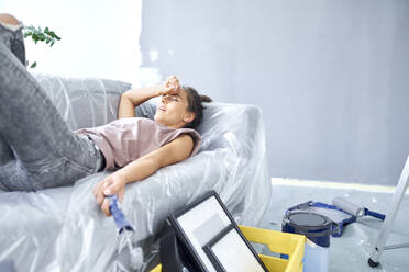 Tired woman holding paint roller while resting on sofa at home - BSZF01751