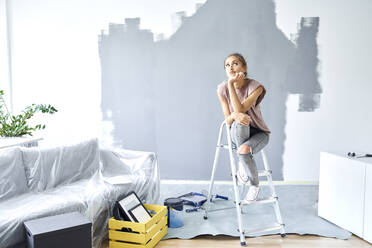 Thoughtful woman with head in hands sitting on ladder against wall at home - BSZF01757