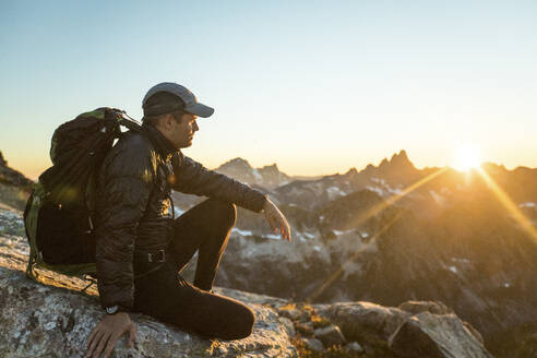 Fit active man sitting on rocky mountain ridge watching the sunset. - CAVF89991
