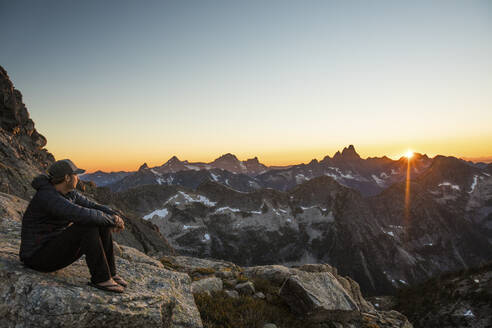 Active fit man resting on rock in mountains watching sunset. - CAVF89994