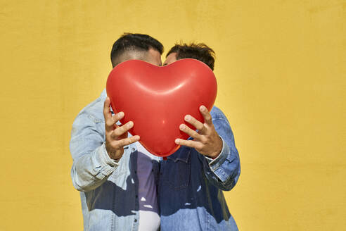 Gay men holding balloon while kissing against yellow wall - VEGF03046