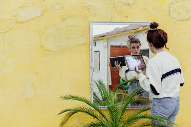 Young woman looking at mirror with make up palette standing in back yard - MRRF00585