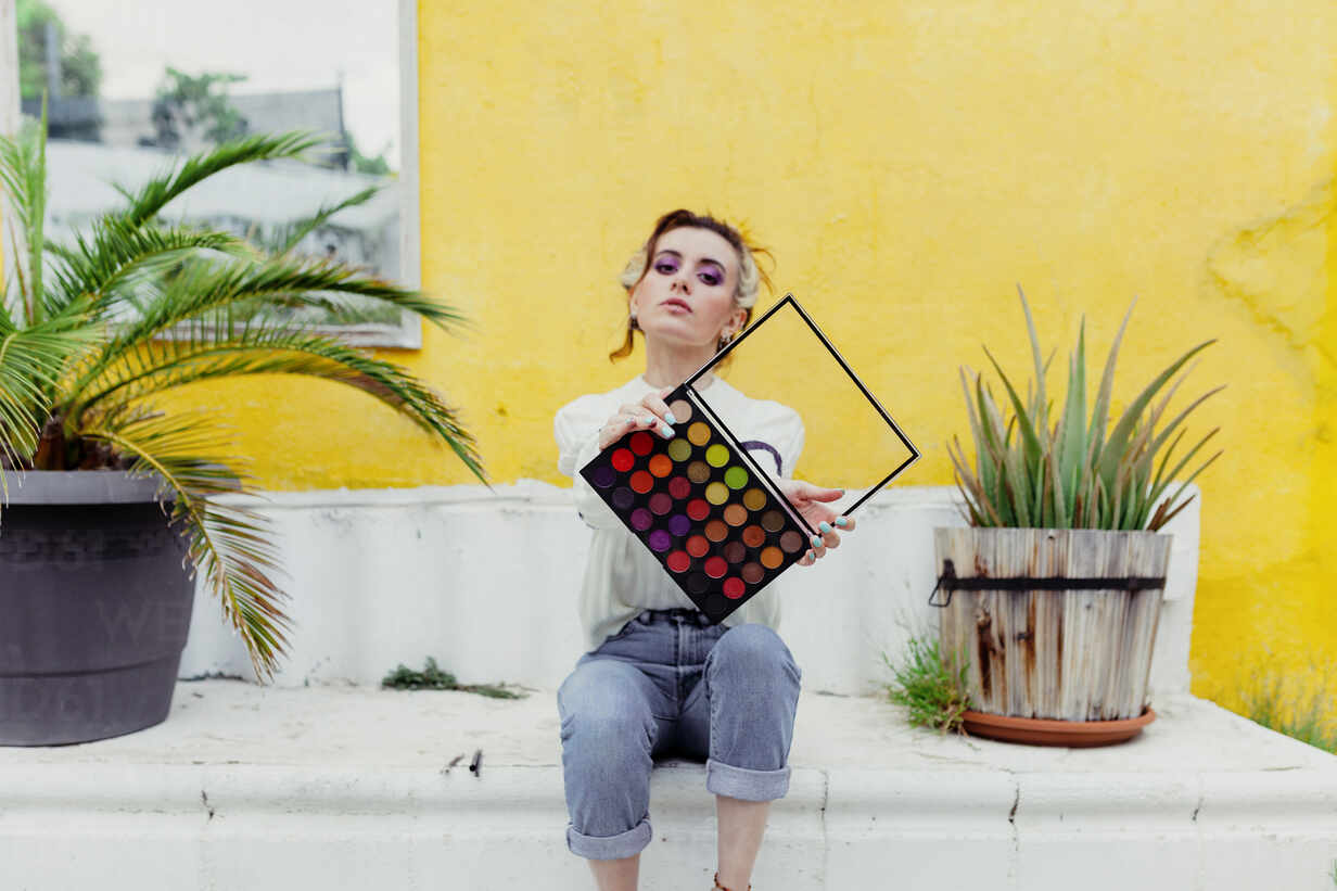 Beautiful woman sitting with make up palette in back yard - MRRF00588 - Manu Reyes/Westend61