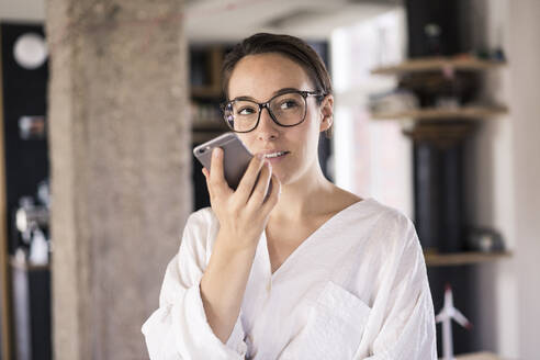 Business woman talking on mobile phone while standing at office - MOEF03510