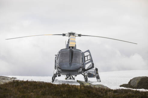 Helicopter landed on snowy mountain ridge. - CAVF90035
