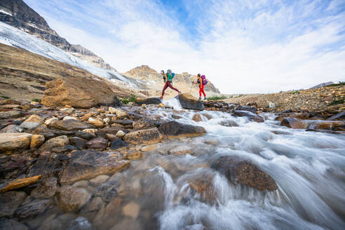 Female Backpackers Crossing River While Hiking Beautiful Iceline Trail - CAVF90119