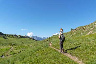 Father carrying daughter on shoulder while hiking in mountain during sunny day - GEMF04295
