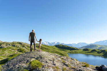 Father and daughter standing on rock object looking at view against clear sky - GEMF04304