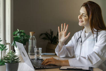 Young female doctor waving hand at patient while providing online consultation from home office - AFVF07374