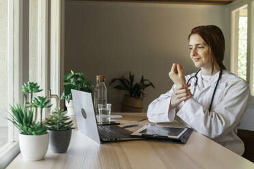 Young female doctor holding wrist while explaining during online consultation at home office - AFVF07377