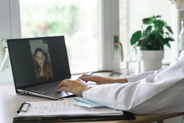 Young female doctor using laptop while talking to patient during online consultation - AFVF07383