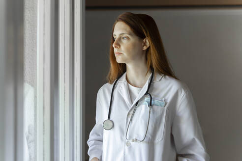 Thoughtful young female doctor looking through window while standing at home office - AFVF07386