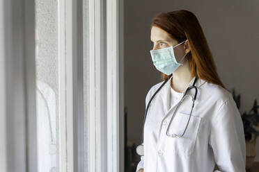 Young female doctor in protective face mask looking through window during COVID-19 - AFVF07392