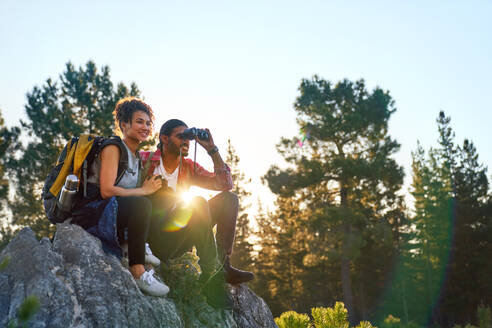 Young couple hiking with binoculars on rocks in sunny woods - CAIF29825