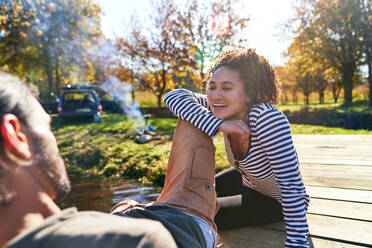 Happy young couple relaxing on sunny autumn dock - CAIF29834