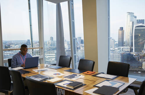 Businessman working at laptop in highrise conference room, London, UK - CAIF29981