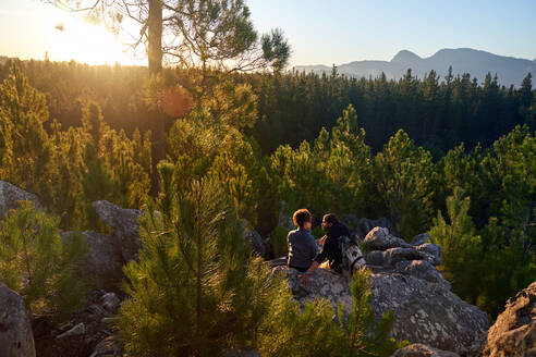 Young hiking couple relaxing on rock in sunny scenic woods - CAIF30011