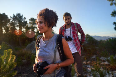 Young couple hiking with camera and binoculars in sunny nature - CAIF30029