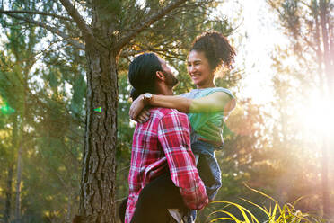 Affectionate young man holding happy girlfriend in sunny woods - CAIF30056