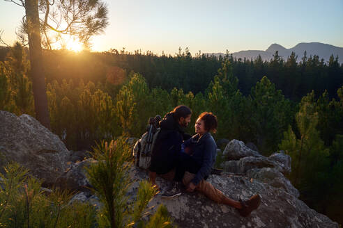 Happy affectionate young couple relaxing on rocks in woods at sunset - CAIF30074