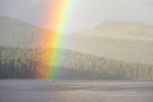 Vivid rainbow shining over calm lake with boat near shore with forest - CAVF90165