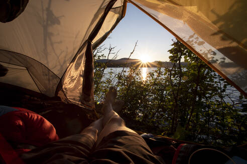 Man watches sunrise from tent near bushes on lake shore in morning - CAVF90168