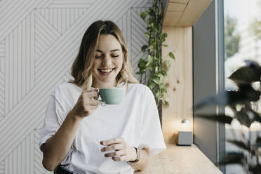 Smiling young woman holding coffee cup while standing in cafe - LHPF01310