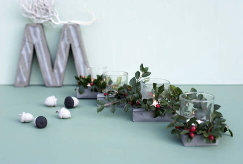 Concrete letter M, painted acorns and candles inside glasses decorated with twigs of cotoneaster - GISF00672