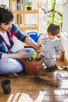 Man putting mud in strawberry plant pot while sitting by boy at balcony - FLMF00318