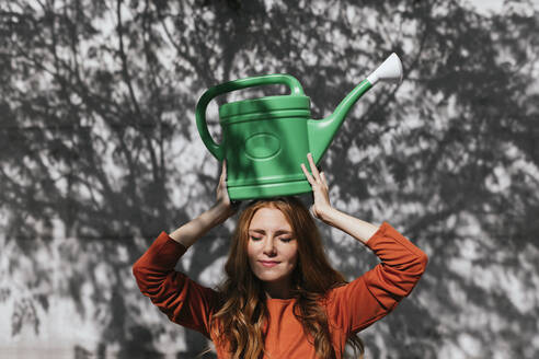 Redhead woman carrying watering can on head while standing against tree shadow wall - TCEF01215