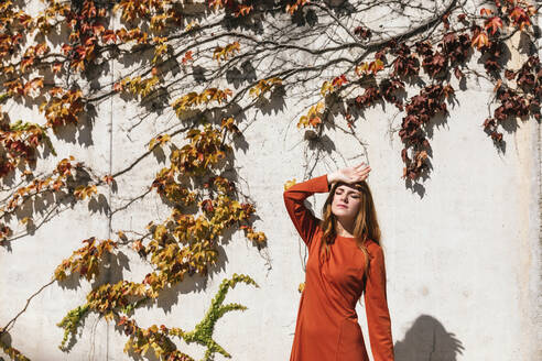Woman with hand on head standing against ivy wall - TCEF01233