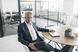 Confident businessman sitting on chair by table at office - GUSF04474