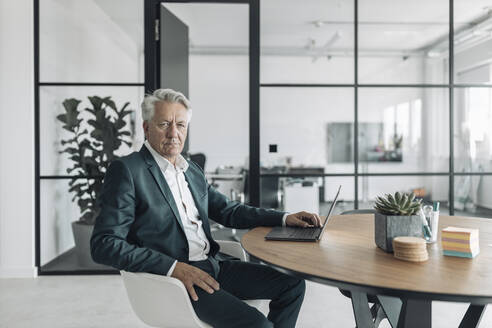 Senior man wearing suit using laptop while sitting on chair at office - GUSF04477
