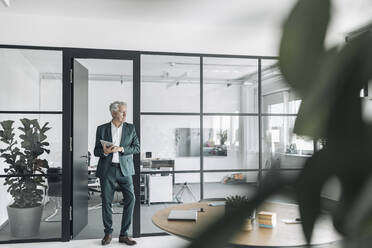 Businessman looking away while using digital tablet at office - GUSF04483