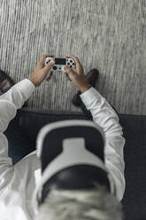 Businessman wearing virtual reality eyeglasses while playing video game at office - GUSF04507