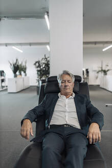 Businessman with eyes closed relaxing on arm chair at office - GUSF04510