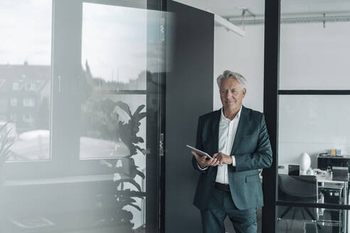 Smiling businessman using digital tablet while standing at office - GUSF04519