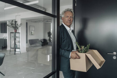 Businessman holding box of botany plant while leaning on glass wall at office - GUSF04528