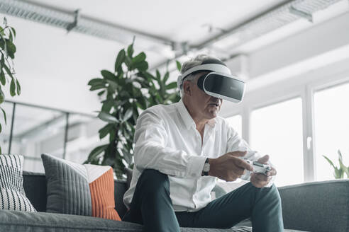 Senior businessman playing video game with virtual reality eyeglasses at office - GUSF04546