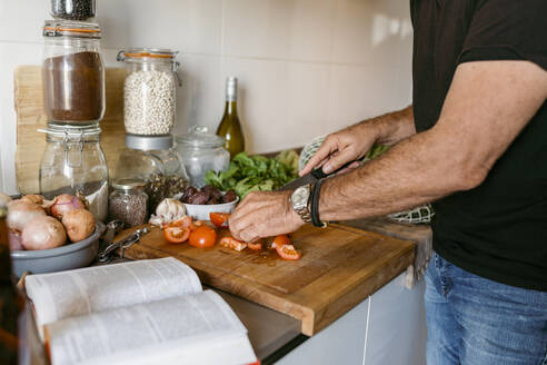 Midsection of man cutting tomato while standing in kitchen at home - VABF03647