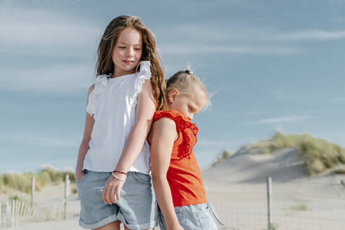Sisters looking down while standing on beach during sunny day - OGF00610
